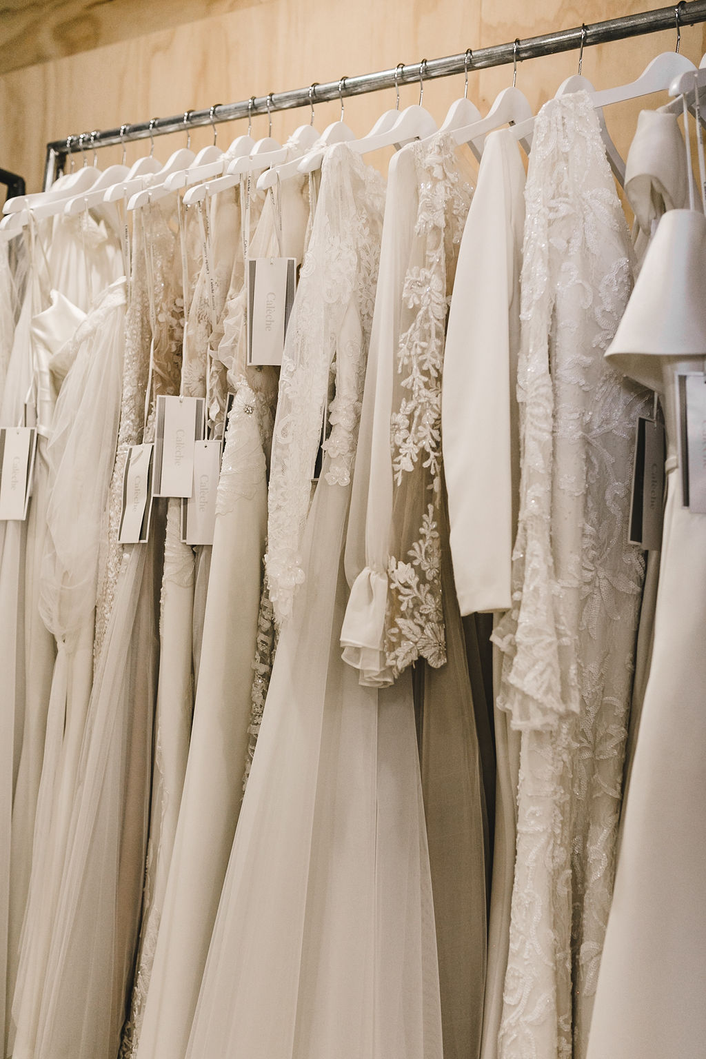 Rack of bridal gowns in Calèche boutique